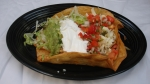 Fajita Taco Salad - A crisp flour tortilla with cheese, topped with steak or chicken cooked with onions, peppers and tomatoes. Covered with lettuce, sour cream, pico de gallo and guacamole.